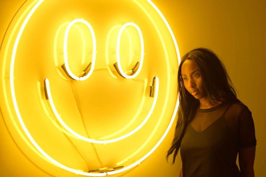 Amber Social in front of a bright smiley face